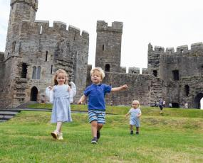 Castell Caernarfon / Caernarfon Castle interior - children running across grass