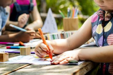 young child colouring in outside